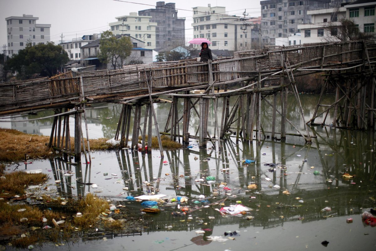 a-woman-walks-on-a-bridge-over-a-polluted-river-at-a-suburban-area-of-wenzhou-in-zhejiang-province