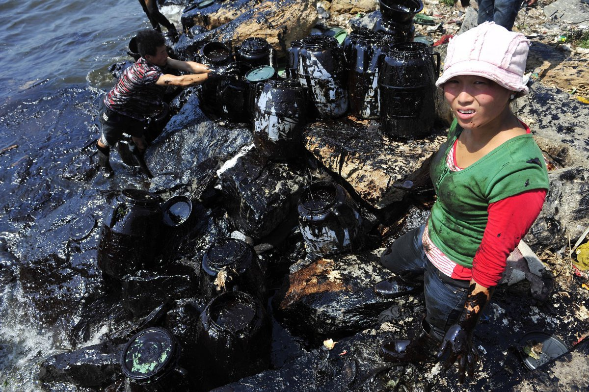 fishermen-clean-up-oil-near-a-major-northern-chinese-port-after-a-pipeline-blast-leaked-more-than-1600-tons-of-heavy-crude-into-the-sea-in-july-2010